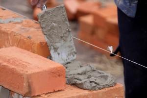Выкладывание кирпичных рядов при возведении стен